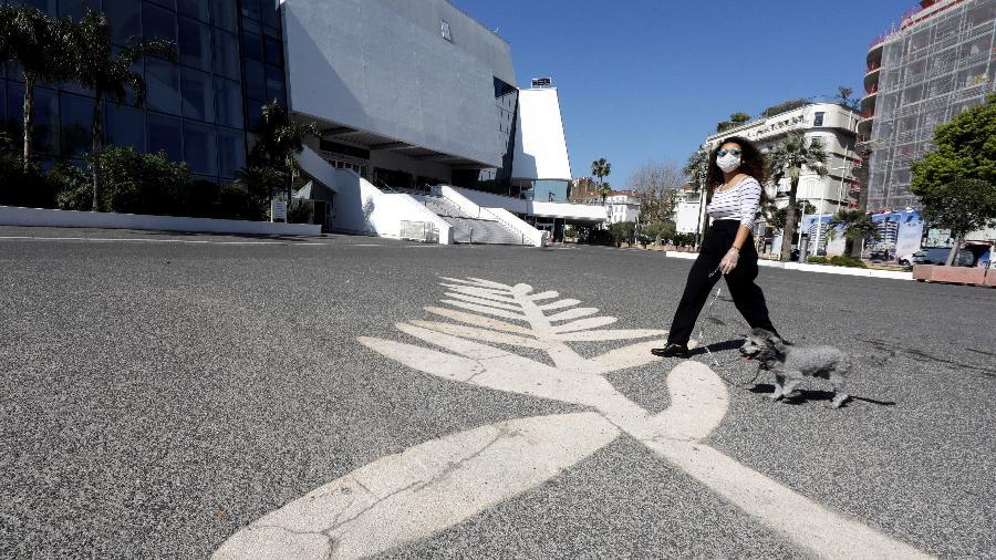 Mulher usando máscara de proteção passeia com cachorro sobre símbolo da Palma de Ouro em frente ao Palácio do Festival em Cannes -