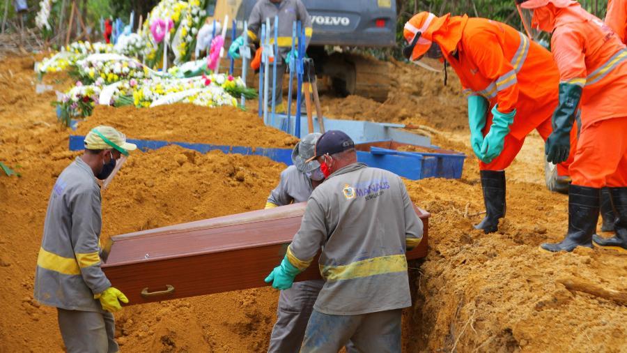 27/04/2020 - Coronavírus: Movimentação no cemitério Parque de Manaus, com coveiros colocando caixões dentro de vala aberta - SANDRO PEREIRA/FOTOARENA/ESTADÃO CONTEÚDO