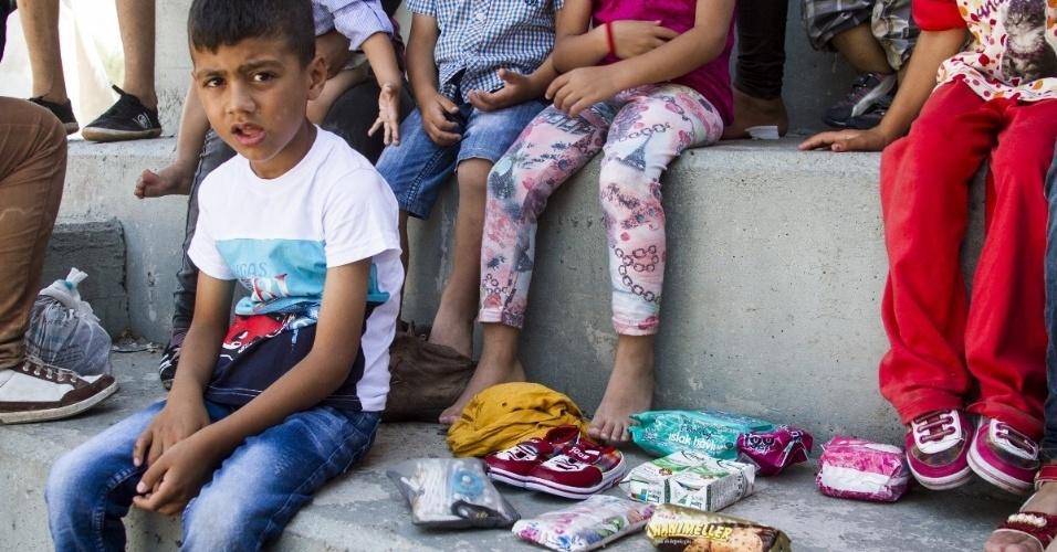 """Essa família proveniente de Aleppo, que não quis dar o nome, perdeu tudo durante a travessia da Síria para Turquia e depois para Grécia. As sete mulheres, os quatro homens e as 20 crianças levavam de uma a duas malas cada um em uma embarcação que afundou durante a viagem. Na única mala que conseguiram salvar, havia uma camiseta, um par de jeans, um par de tênis, um pacote de fraldas, duas pequenas embalagens de leite e alguns biscoitos, além de um pacote de absorventes e um pente. """"Eu espero que a gente morra. Esta vida não vale mais viver. Todos fecharam as portas na nossa cara, não há futuro"""", disse um dos familiares"""