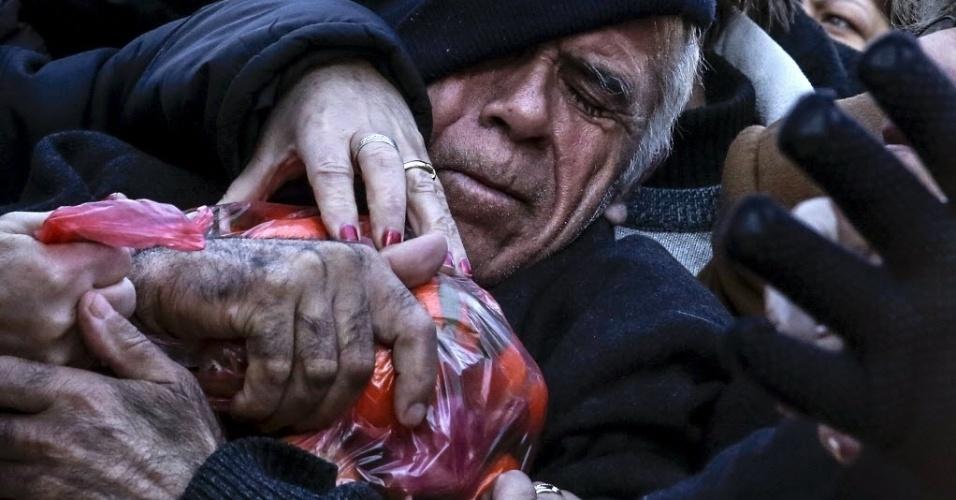28.jan.2016 - Homem briga por saco de frutas durante protesto de agricultores contra a proposta do governo de reformar o sistema de recebimento de pensão em Atenas, Grécia