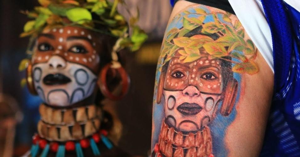 20.jun.2016 ? Um homem mostra sua nova tatuagem ao lado da modelo usada como inspiração na Mostra Anual de Tatuagens em Toronto, no Canadá. A feira dura três dias e atrai mais de 400 artistas de todo o mundo