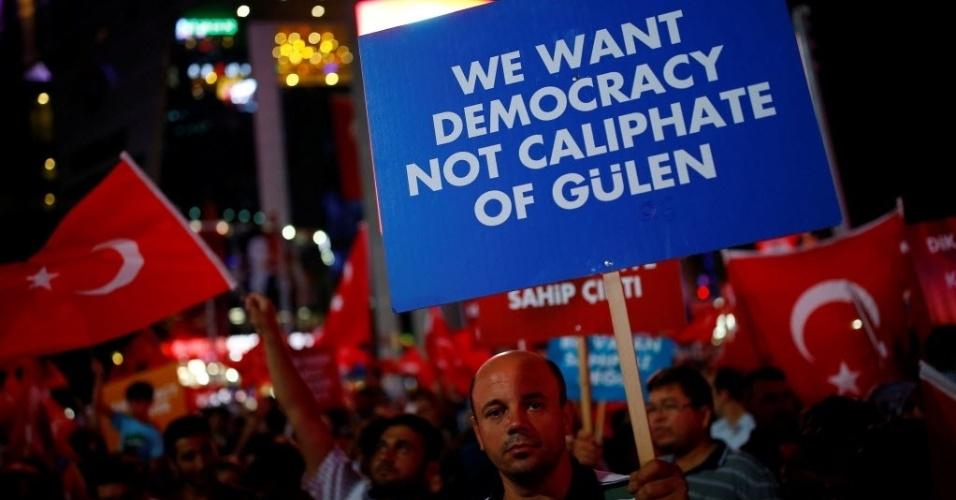 """27.jul.2016 - Homem segura uma placa onde se lê, em inglês, """"Nós queremos democracia, não um califado de Gülen"""", durante protesto no centro de Ancara, na Turquia. A placa faz referência ao líder dissidente Fethullah Gülen, tido pelo governo turco como mentor da tentativa de golpe de Estado ocorrida no dia 15 de julho. Desde então, turcos tem se reunido nas ruas da capital para protestar contra o golpe"""