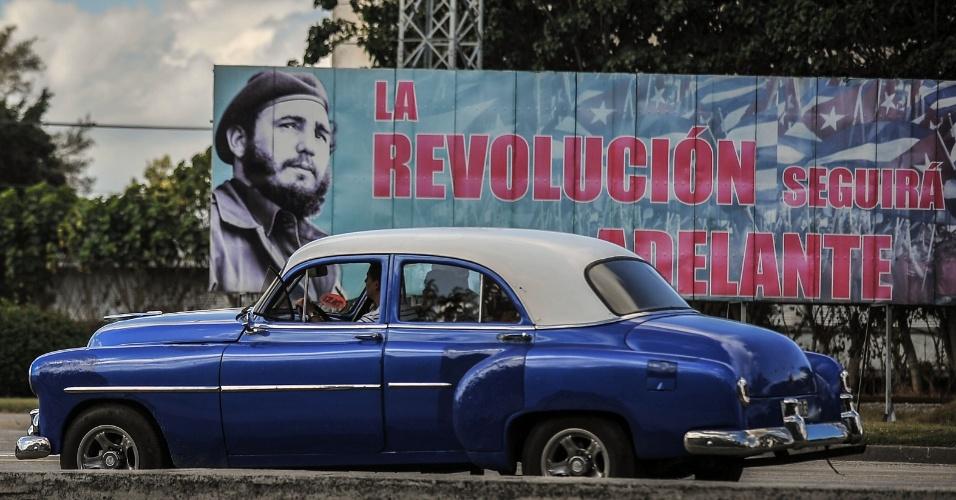 """27.nov.2016 - Um carro antigo passa em frente ao outdoor que anuncia """"A Revolução seguirá adiante"""" em Havana"""