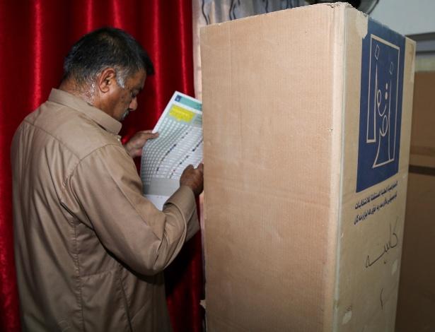 Iraquiano confere cédula de votação ao entrar para votar neste sábado, em Bagdá