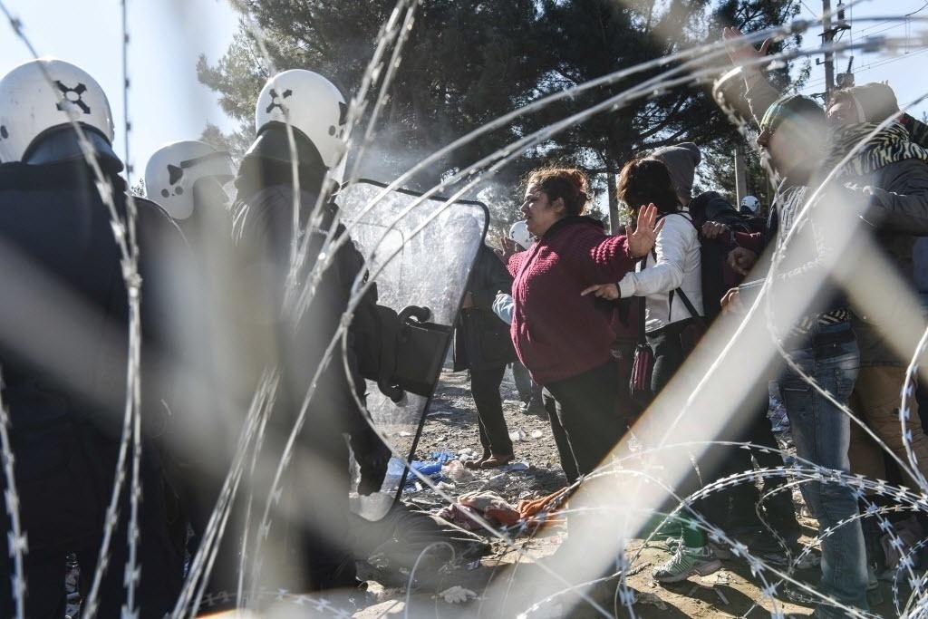 3.dez.2015 - Mulher abre os braços em frente a policiais enquanto imigrantes tentam cruzar a fronteira entre a Grécia e a Macedônia, no vilarejo grego de Idomeni