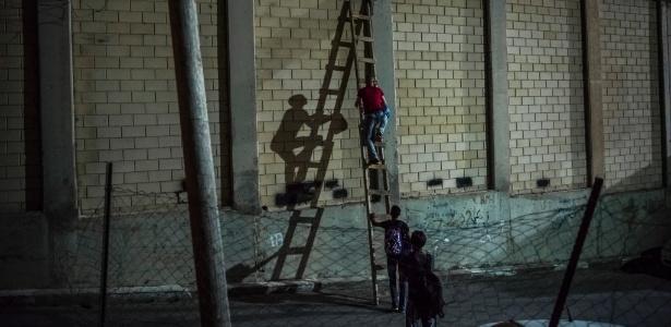 7.jun.2016 - Contrabandista atravessa trabalhadores palestinos por segmento do muro que separa Israel da Cisjordânia