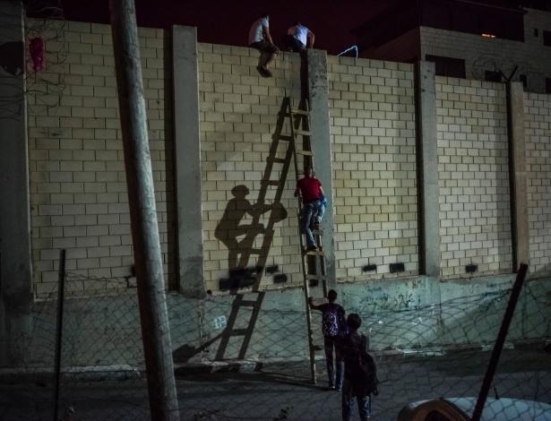 Contrabandista atravessa trabalhadores palestinos por segmento do muro que separa Israel da Cisjordânia