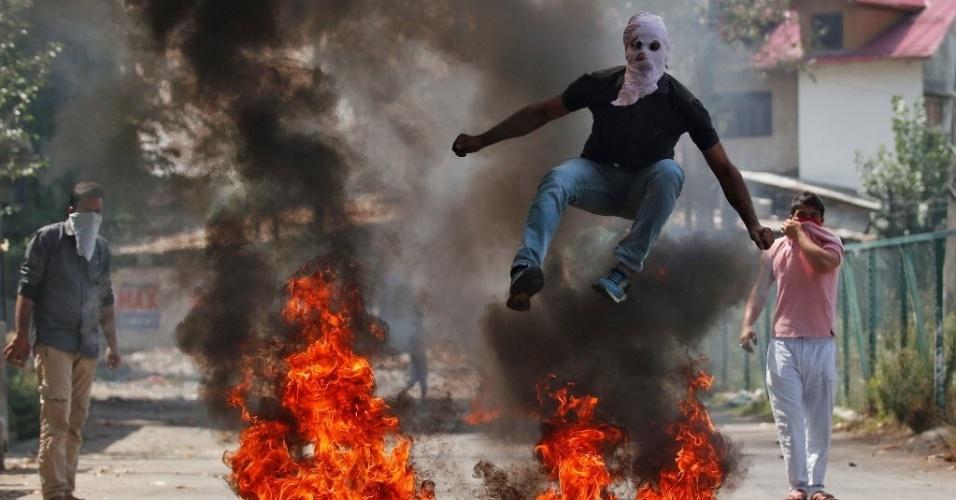 12.set.2016 - Homem mascarado pula barricada feita com objetos em chamas durante protestos em Srinagar, na região da Caxemira, na Índia