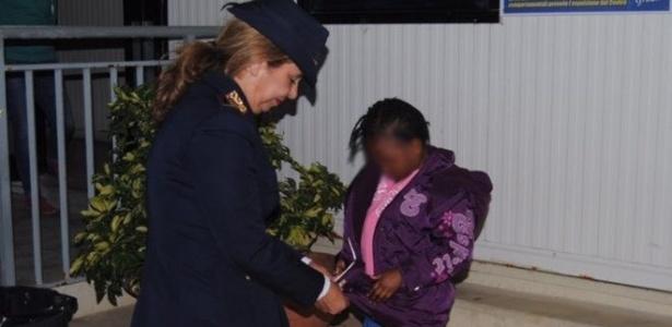 A policial italiana Maria Volpe cuida da pequena Oumoh, que aguarda apenas o resultado do teste de DNA para reencontrar a mãe.
