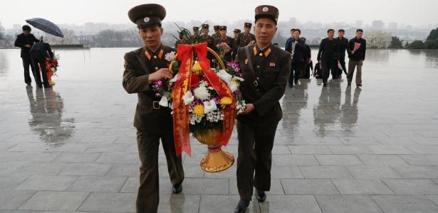 14.abr.2017 - Soldados carregam flores ao chegar para homenagens junto às estátuas do fundador da Coreia do Norte, Kim Il-sung, em Pyongyang