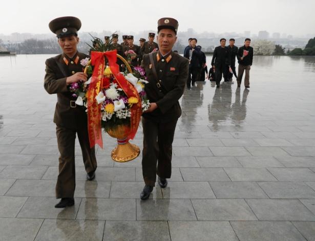 Soldados carregam flores ao chegar para homenagens junto às estátuas do fundador da Coreia do Norte, Kim Il-sung, em Pyongyang