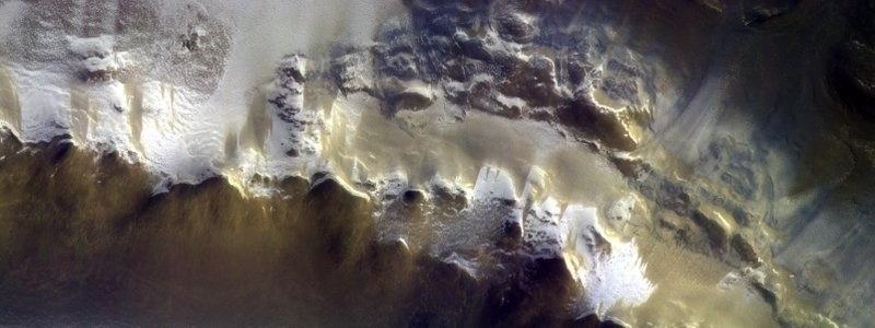 TEM METANO EM MARTE? - A ESA (Agência Espacial Europeia) divulgou a primeira foto tirada pelo módulo Trace Gas Orbiter, que investiga se a atmosfera marciana possui gases como o metano, o que pode indicar a existência de atividade biológica ou geológica. A câmera fotográfica é um dos quatro instrumentos a bordo do satélite. Além de permitirem a investigação das áreas onde os gases forem encontrados, as fotos ajudarão também na escolha de futuros locais de pouso de sondas e rovers. A imagem acima mostra a cobertura de gelo na cratera Korolev, próximo ao polo norte, vista a uma altitude de 400 km.