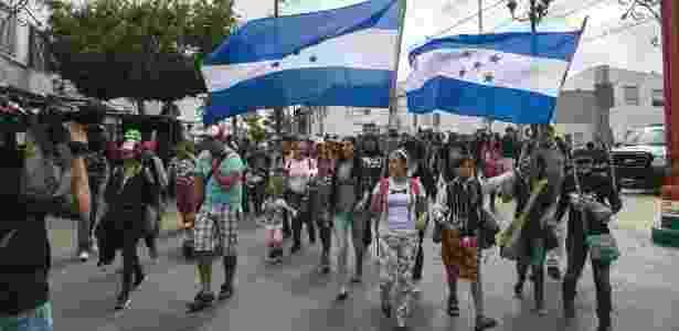Imigrantes hondurenhos seguram bandeira do país na fronteira dos EUA com Tijuana, no México  - Meghan Dhaliwal/The New York Times - Meghan Dhaliwal/The New York Times