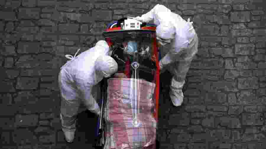 Médicos utilizam equipamentos de proteção enquanto transferem paciente infectado com o novo coronavírus em Seul, na Coreia do Sul - Chung Sung-Jun/Getty Images