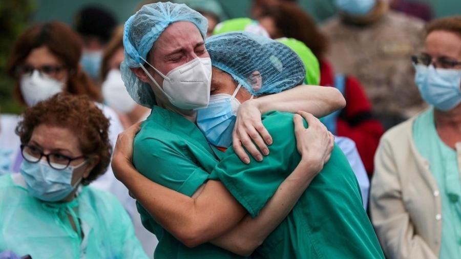 Profissionais de saúde se abraçam após a morte de um colega na Espanha - Susana Vera/Reuters