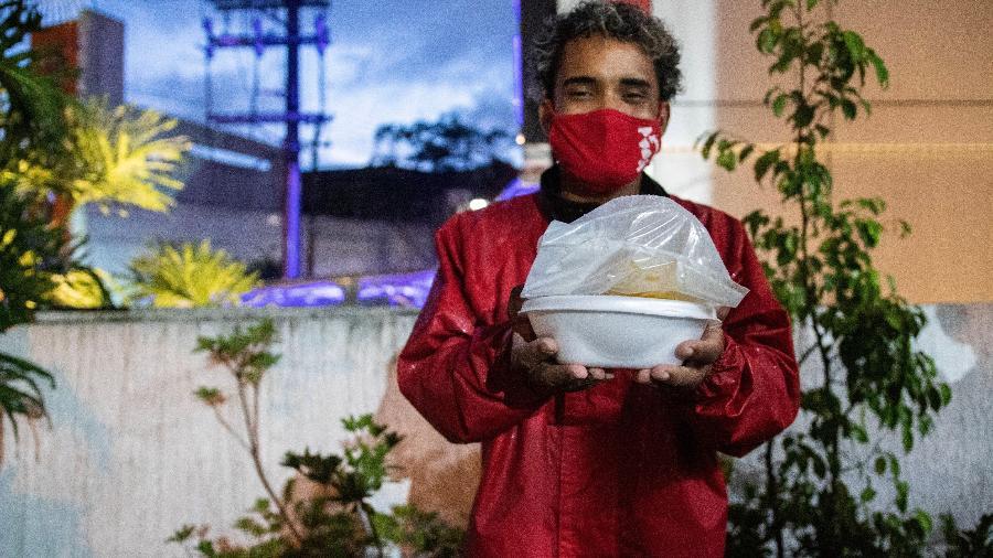 O entregador Matheus dos Santos exibe a janta do sábado: macarrão à bolonhesa, feijão, purê de batata, pudim de pão e suco de laranja - Lucas Guarnieri Marteli