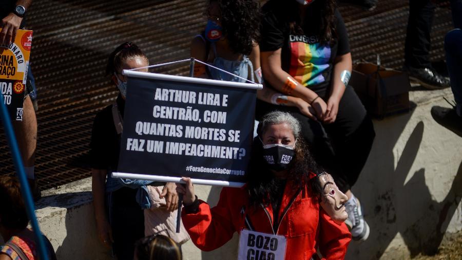 """Manifestante segura cartaz onde se lê """"Arthur Lira e Centrão, com quantas mortes se faz um impeachment"""", no Rio - ERBS Jr/FramePhoto/Estadão Conteúdo"""
