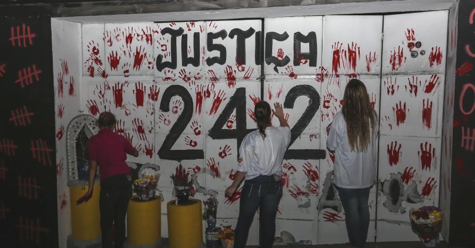 27.jan.2016 - Familiares de vítimas e sobreviventes do incêndio na boate Kiss fazem vigília em frente ao local da tragédia, em Santa Maria (RS), para lembrar os três anos do episódio que matou 242 pessoas. O grupo se reuniu em círculo e, de mãos dadas, rezou. Mais cedo, o número 242 e a palavra justiça foram escritos na fachada do prédio, acompanhados de marcas de mãos na cor vermelha que participantes da vigília pintaram na parede