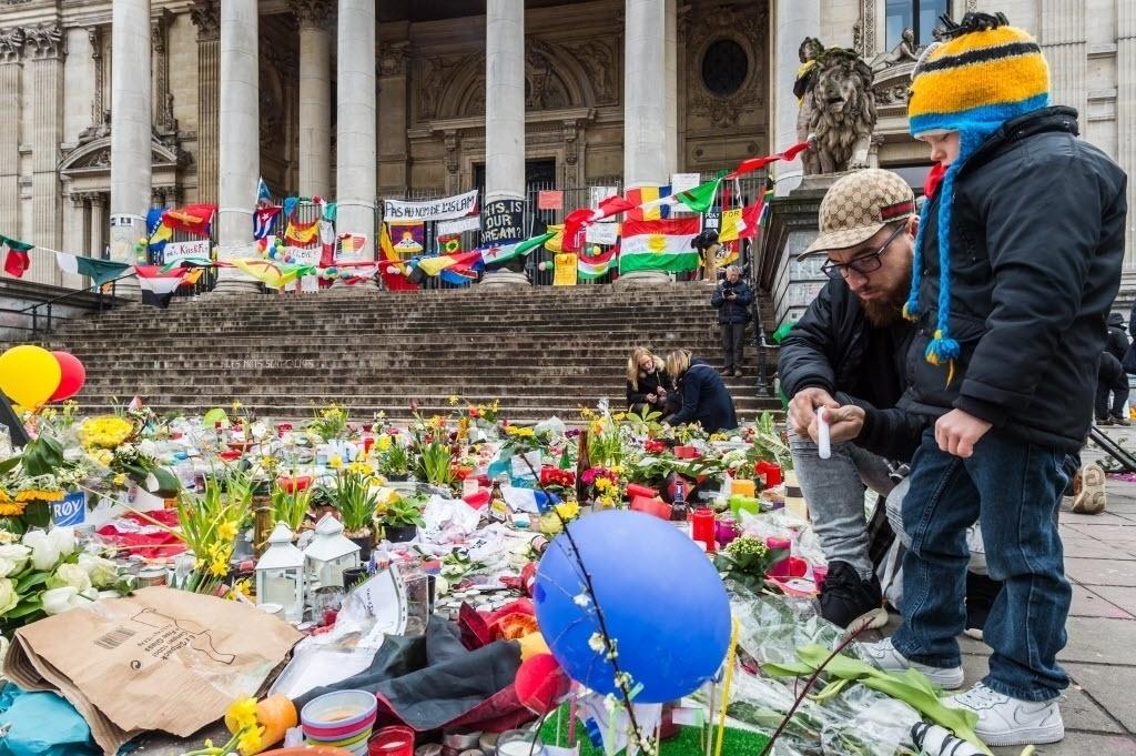 27.mar.2016 - Um homem pede ajuda de criança para acender uma vela em homenagem aos mortos nos ataques com bomba em Bruxelas, na Bélgica. Após os atentados que mataram ao menos 30 pessoas, a cidade segue com segurança reforçada