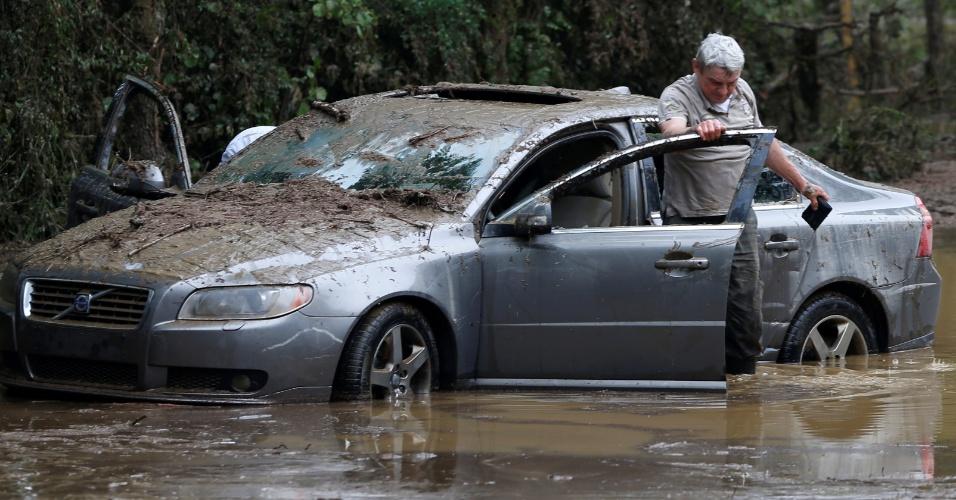 3.jun.2016 - Homem busca pertence de dentro de carro arrastado pela enchente após fortes chuvas na cidade de Nassogne, na Bélgica