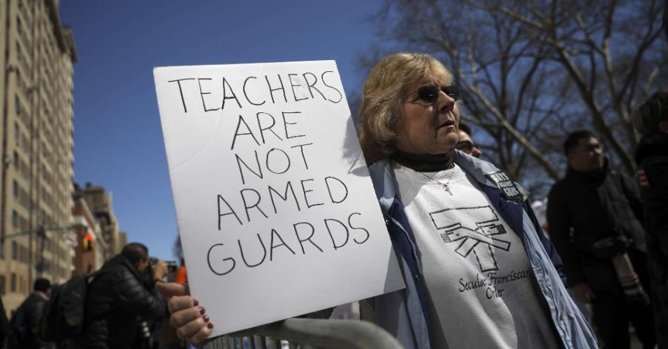 """24.mar.2018 - """"Professores não são guardas armados"""", diz a placa levada à marcha pela manifestante em Nova York. Milhares de estudantes, professores e seus parentes participaram dos protestos em cidades dos EUA contra as armas de fogo"""