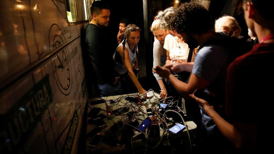 26.mar.2019 - Pessoas tentam carregar seus celulares em um gerador em uma praça pública durante o apagão em Caracas, na Venezuela - Carlos Garcia Rawlins/Reuters