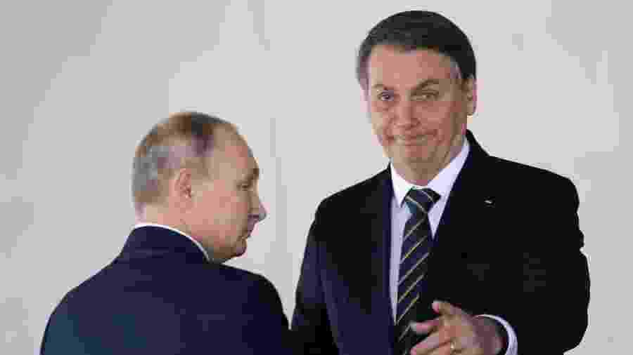 Bolsonaro aponta para fotógrafos ao cumprimentar Vladimir Putin - ADRIANO MACHADO/Reuters