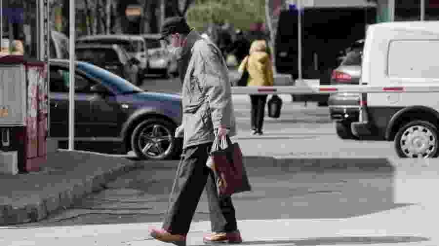 Idoso caminha pela ruas em meio à pandemia do novo coronavírus - NurPhoto via Getty Images