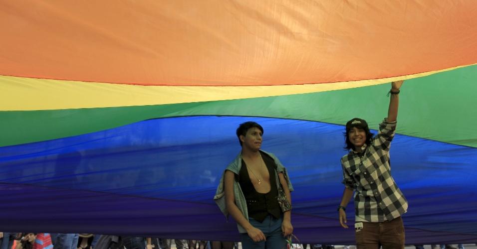 28.jun.2015 - Participantes tocam uma bandeira gigante com as cores do arco-íris durante Parada do Orgulho Gay em San José, na Costa Rica, neste domingo (28)