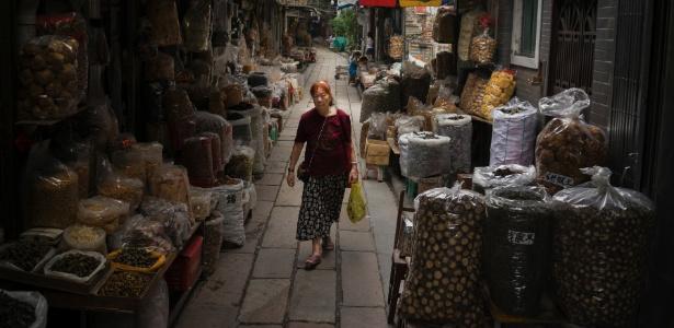 Mulher caminha por barracas que vendem ingredientes tradicionais usados na medicina chinesa em Guangzhou, na China