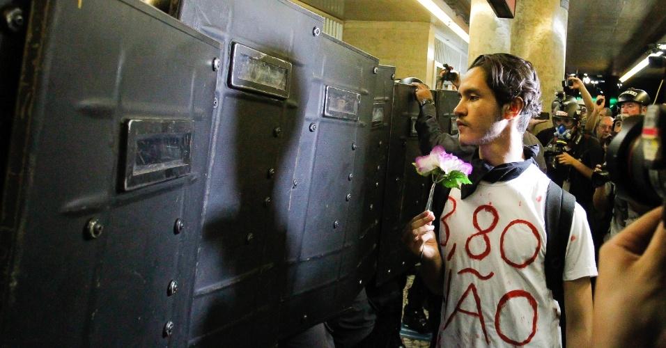 26.jan.2016 - Em meio à confusão no metrô e bloqueio de policiais com escudo, um manifestante realiza ato pacífico: simbolicamente, oferece uma flor à tropa que se negava a deixar manifestantes e pessoas comuns entraram no metrô Anhangabaú
