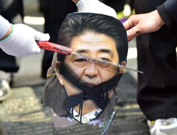 1.abr.2015 - Manifestantes sul-coreanos cortam figura do premiê japonês, Shinzo Abe, durante protesto contra o Japão em Seul