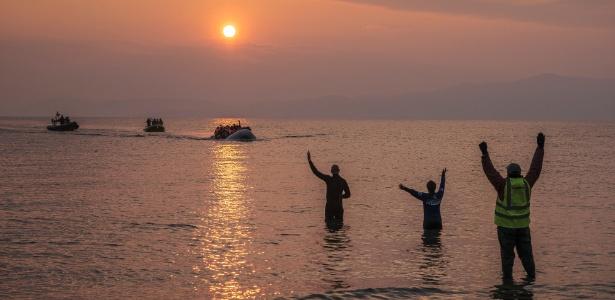 Resgatistas recepcionam barcos cheios de refugiados que chegam à ilha de Lesbos, na Grécia