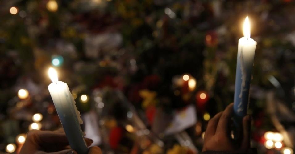 25.mar.2016 - Dupla acende velas na praça la Bourse, em Bruxelas, para prestar homenagem às vítimas do atentado terrorista que matou mais de 30 pessoas com explosões no metrô e aeroporto da cidade