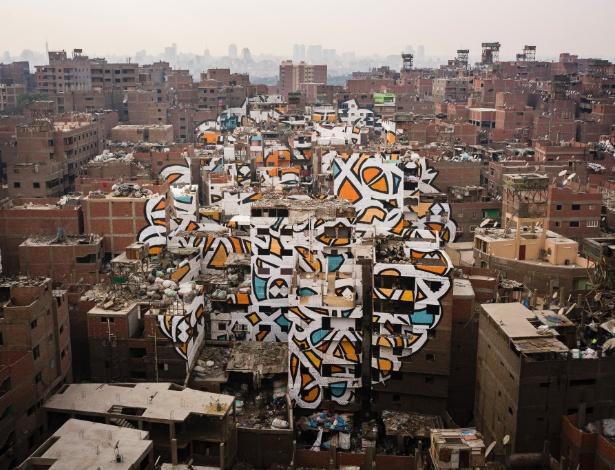 Mural que se estende por mais de 50 construções foi criado pelo artista eL Seed no distrito Manshiyat Naser, na cidade do Cairo (Egito), lar de catadores de lixo