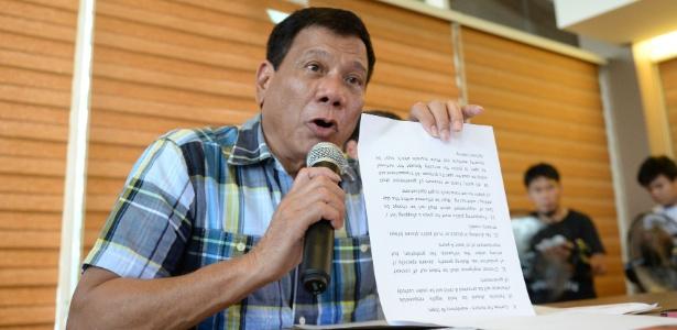 O presidente eleito das Filipinas, Rodrigo Duterte, mostra documento durante coletiva em Davao