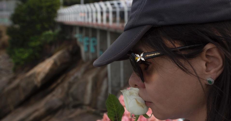 19.jun.2016 - Mulher joga rosa branca no local do desabamento da ciclovia Tim Maia, na zona sul do Rio de Janeiro. O desastre, que está prestes a completar dois meses, resultou na morte de duas pessoas. Em uma passeata pela ciclovia, familiares das vítimas exigiam respostas das autoridades