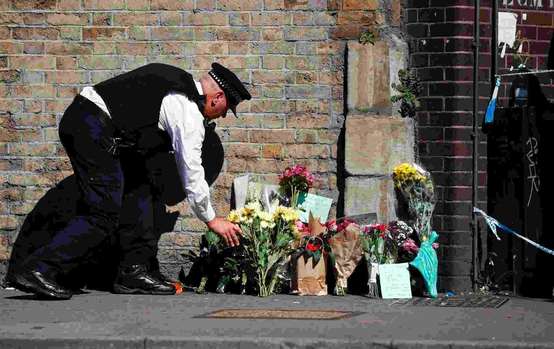 19.jun.2017 - Policial deposita flores dentro da área isolada onde ocorreu o atropelamento de 11 pessoas nesta segunda-feira - Tolga Akmen/AFP Photo