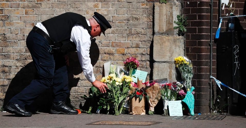 19.jun.2017 - Policial deposita flores dentro da área isolada onde ocorreu o atropelamento de 11 pessoas nesta segunda-feira