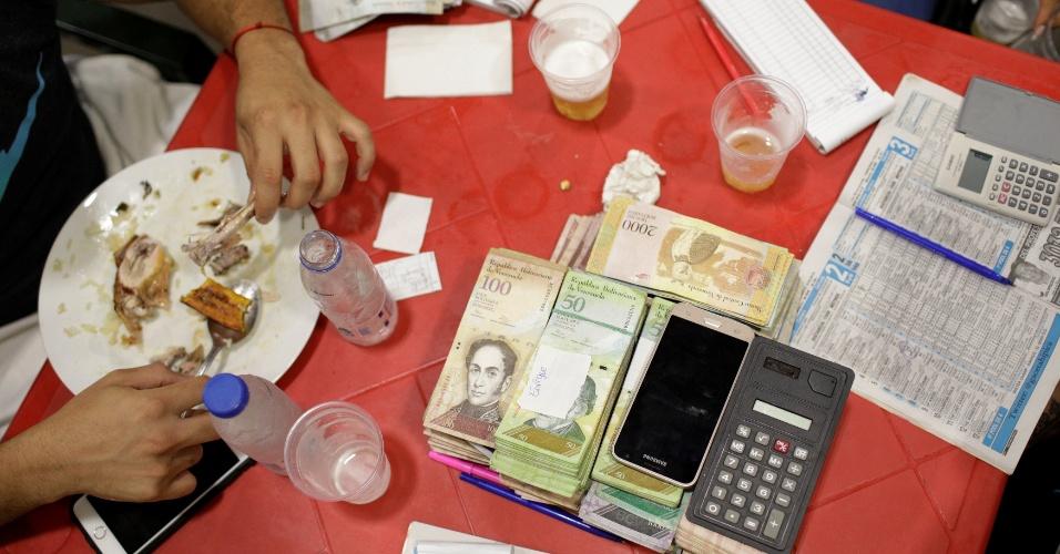 Apostador almoça cercado de dinheiro e anotações de apostas no Hipódromo de La Rinconada, em Caracas, Venezuela
