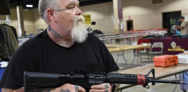 Vendedor da feira faz demostração com o AR-15: vendas aquecidas teriam ligação com temor de que arma seja proibida - AFP