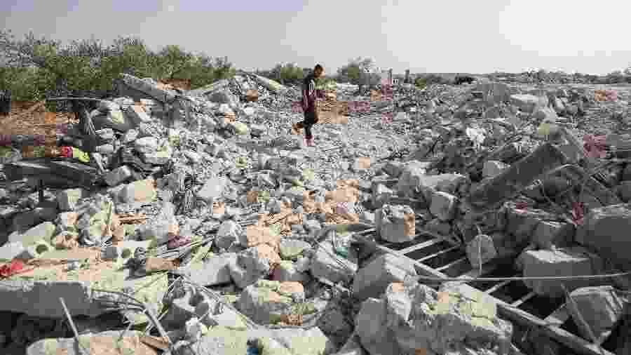27.out.2019 - Sírio caminha por destroços  - Haj Kadour/AFP