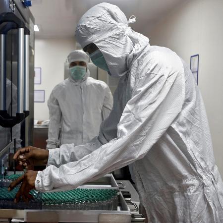 30.nov.2020 - Funcionário com equipamento de segurança remove frascos da vacina contra covid-19 de máquina no laboratório no Instituto Serum, na Índia  - Francis Mascarenhas/Reuters