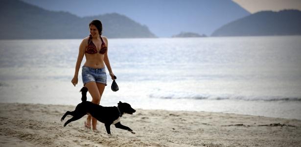 Banhista caminha com cachorro na praia de Maresias, em SP