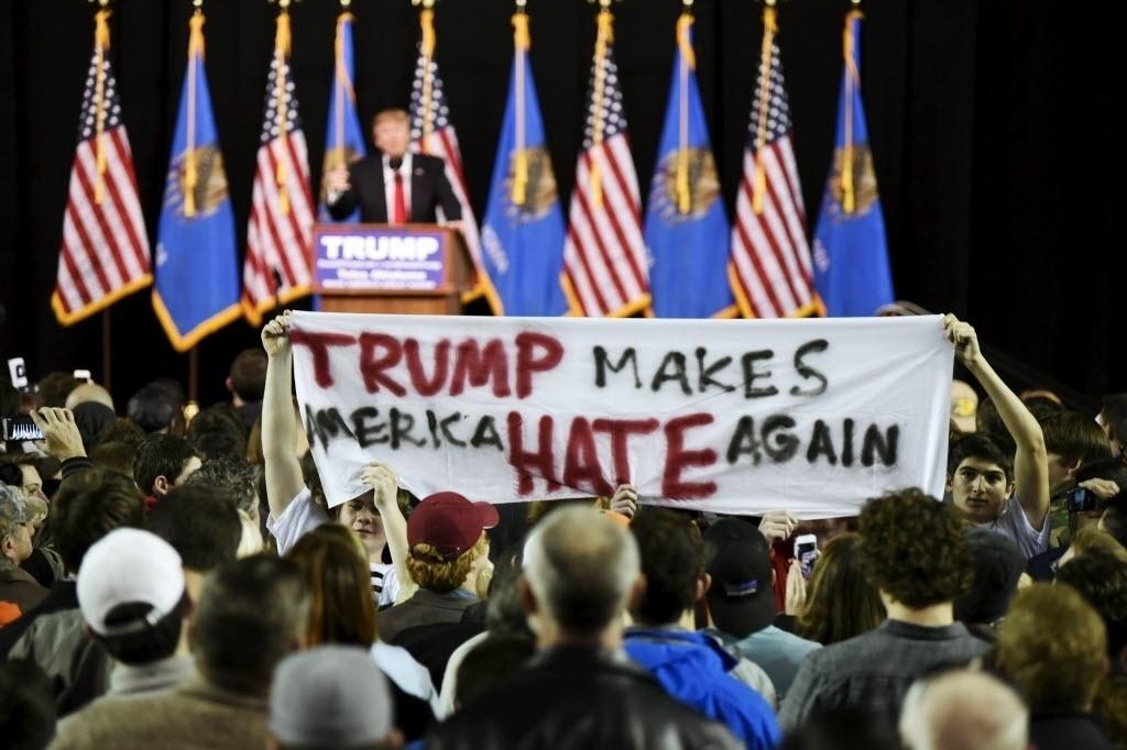 20.jan.2016 - Manifestantes seguraram um cartaz com os dizeres ?Trump faz a América odiar novamente? (em tradução livre do inglês) durante um comício do pré-candidato republicano à Presidência dos Estados Unidos Donald Trump, na Universidade Oral Roberts em Tulsa, nos EUA. O candidato divide opiniões por fazer uma série de declarações xenófobas sobre a imigração latina