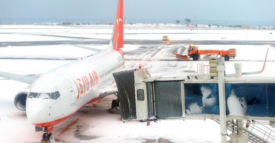 25.jan.2016 - Boeing 737 da companhia aérea Jeju fica estacionado no aeroporto da ilha de Jeju, na Coreia do Sul, em meio uma cobertura de neve que fechou o local pelo terceiro dia consecutivo. Cerca de 86 mil pessoas estão presas na ilha turística em consequência da nevasca mais intensa na região em três décadas
