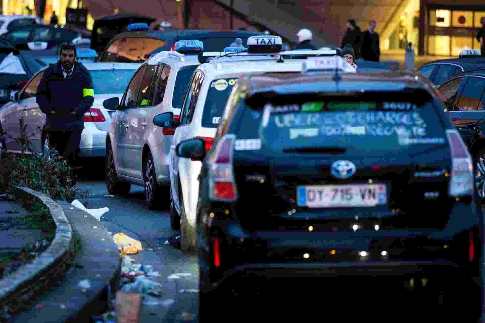 28.jan.2016 - Táxis fecham via durante protesto em Porte Maillot, em Paris, contra serviços de transporte privado. Os taxistas reclamam da concorrência com o aplicativo Uber com outros serviços de táxis não licenciados - Geoffroy Van Der Hasselt/AFP