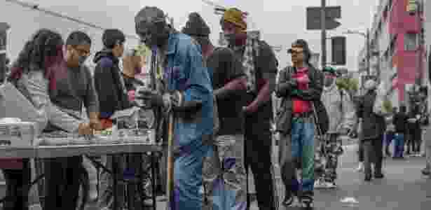 Sem-teto formam fila para receber comida no bairro de Skid Row, centro de Los Angeles - Monica Almeida/The New York Times