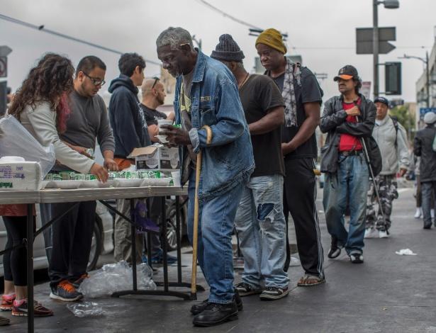 Sem-teto formam fila para receber comida no bairro de Skid Row, centro de Los Angeles