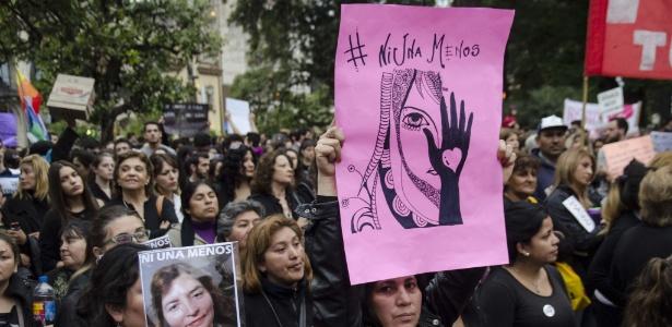 Mulheres levantam cartazes durante o primeiro Ato Nacional de Mulheres em protesto contra feminicídio